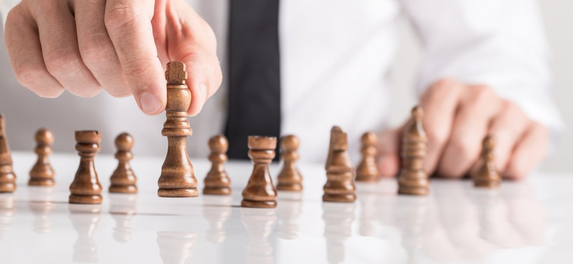 Businessman playing a game of chess on white table in a close up